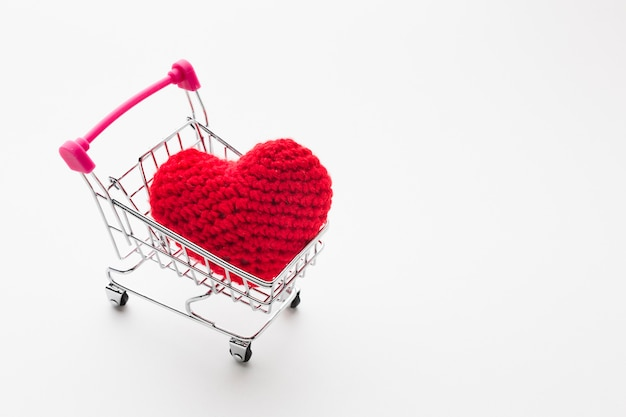 High angle of shopping cart with valentines day ornament