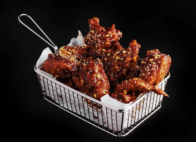 High angle shot of a basket of delicious fried chicken with hot sauce on a black surface