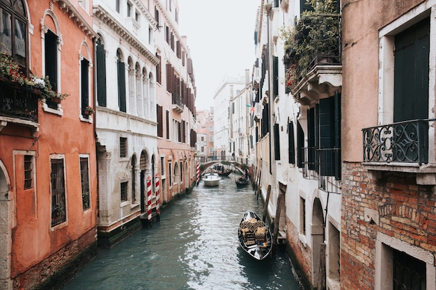 High angle shot of a beautiful canal in venice with gondolas  between two buildings