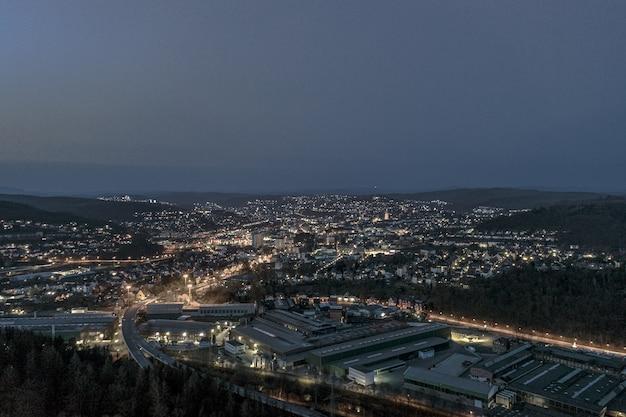 Colpo di alto angolo di una bellissima città circondata da colline sotto il cielo notturno