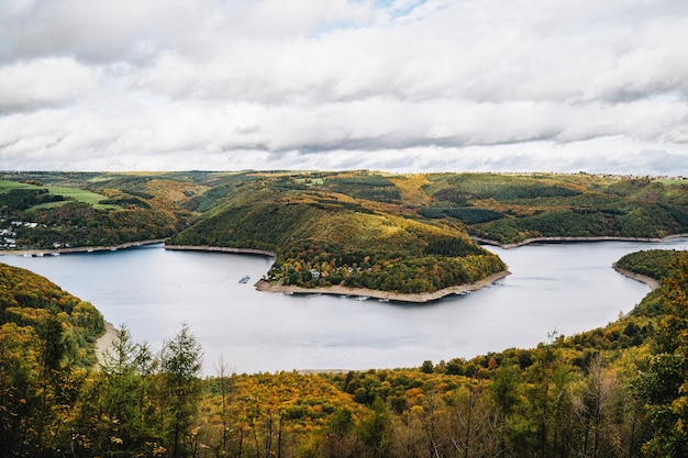 High angle shot of a beautiful lake surrounded by hills in autumn under the cloudy sky