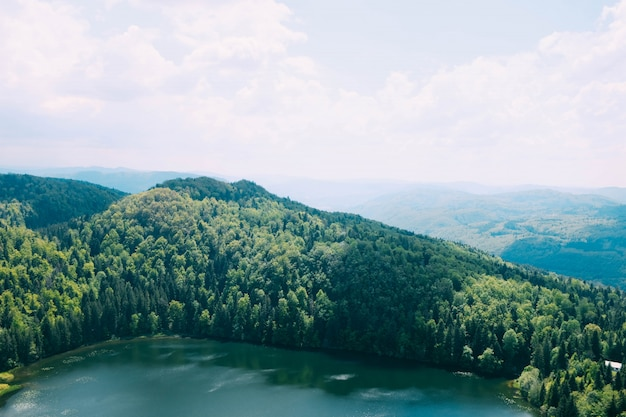 High angle shot of a beautiful lake surrounded by tree covered mountains under the cloudy sky