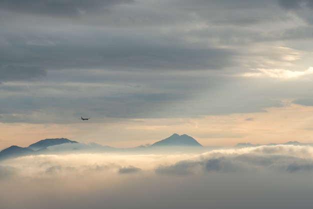 High angle shot of the beautiful mountain tops visible through the clouds and fog