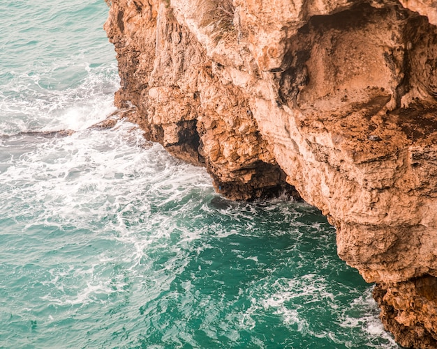 High angle shot of the beautiful rocky cliffs over the ocean captured in italy