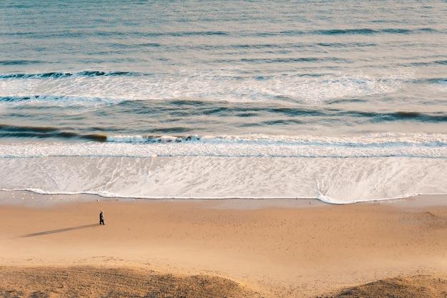 Colpo di alto angolo di un bellissimo oceano ondulato contro una sabbia marrone