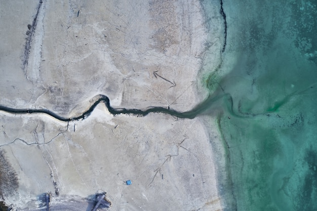 High angle shot of a big crack on the stony shore next to the turquoise water