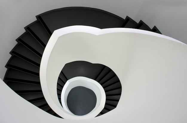 High angle shot of a black stairway going down surrounded by white walls
