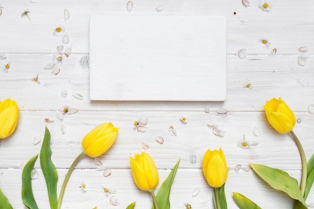 High angle shot of a blank paper with yellow tulips on a white table