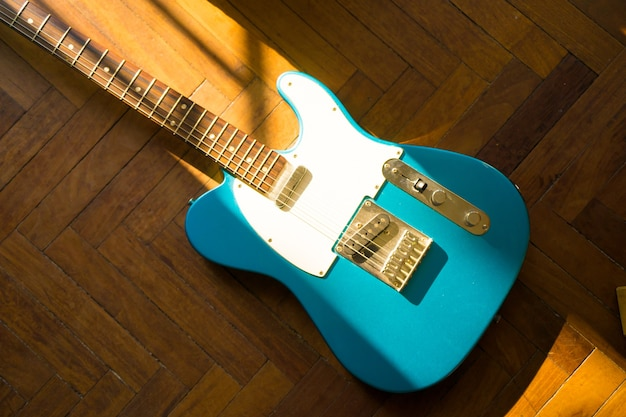 High angle shot of a blue guitar on a wooden surface