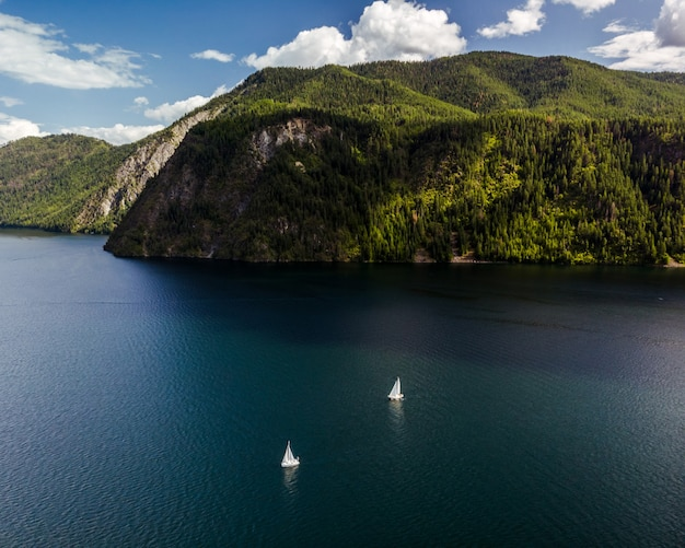 High angle shot of boats sailing on the water with forested mountains in the distance
