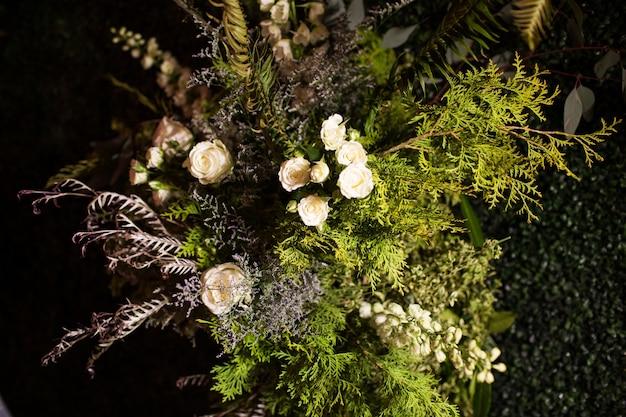 Colpo di alto angolo di un bouquet con foglie sempreverdi e rose bianche sotto le luci