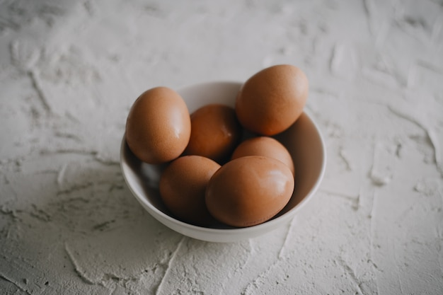 High angle shot of a bowl of eggs on a white surface