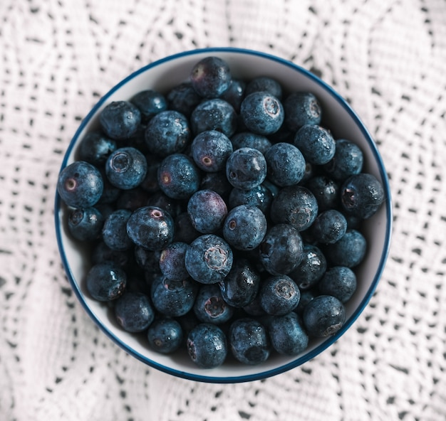 High angle shot of a bowl filled with blueberries on a nice white tablecloth on a table