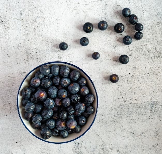 High angle shot of a bowl full of blueberries with some blueberries scattered on a white surface