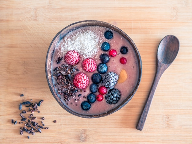 High angle shot of a bowl of muesli with berries on a wooden surface
