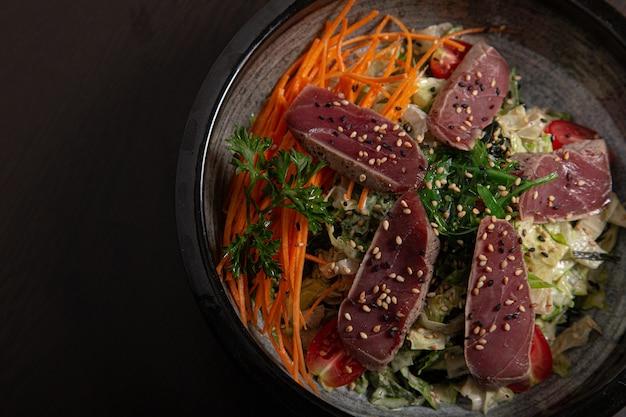 Inquadratura dall'alto di una ciotola di cibo asiatico tradizionale su una superficie nera