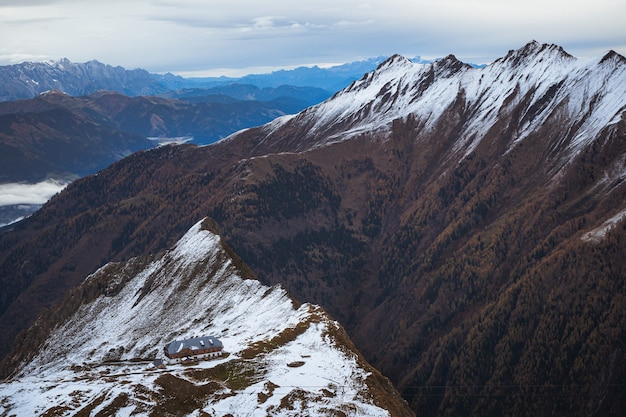 High angle shot of a building on top of a snowy mountain under a cloudy sky