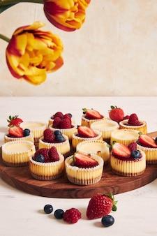 Colpo di alto angolo di cupcakes al formaggio con gelatina di frutta e frutta su un piatto di legno