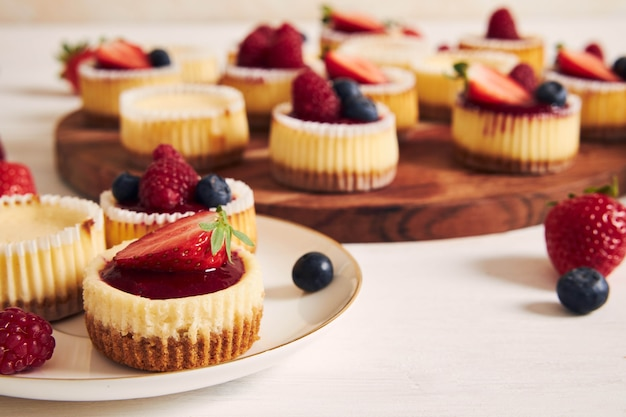 High angle shot of cheese cupcakes with fruit jelly and fruits on a wooden plate