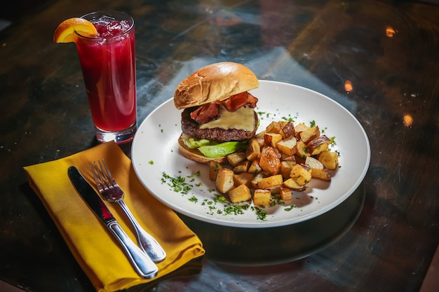 High angle shot of a cheeseburger with potato cubes on the side with a red drink next to it