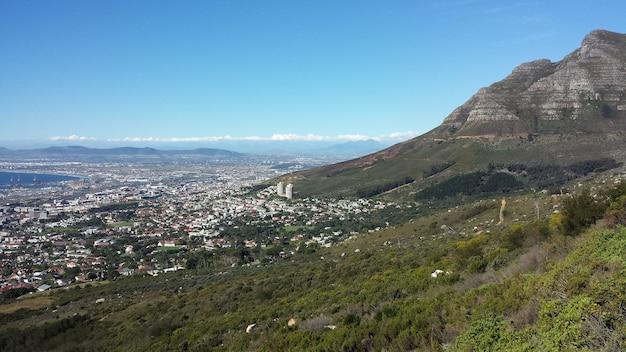 Inquadratura dall'alto di una città ai piedi di una bellissima montagna sotto un cielo blu chiaro