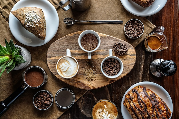 High angle shot of coffee beans in jars on a breakfast table with some pastry