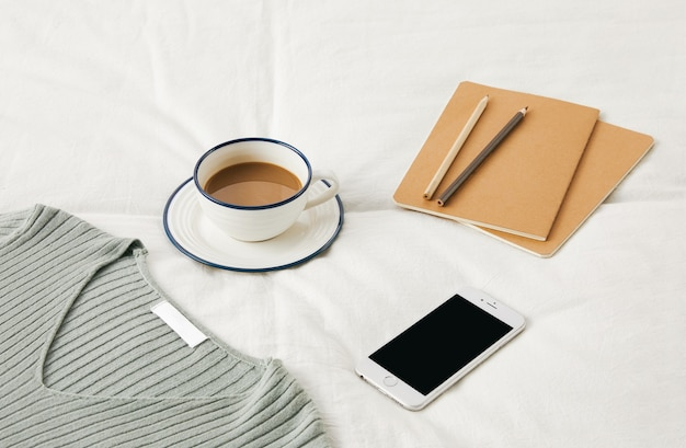 High angle shot of a cup of coffee on bedsheets with sketchbooks, phone, and a sweater on it