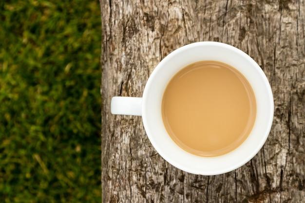 Colpo di alto angolo di una tazza di caffè su una superficie di legno sopra il campo coperto di erba