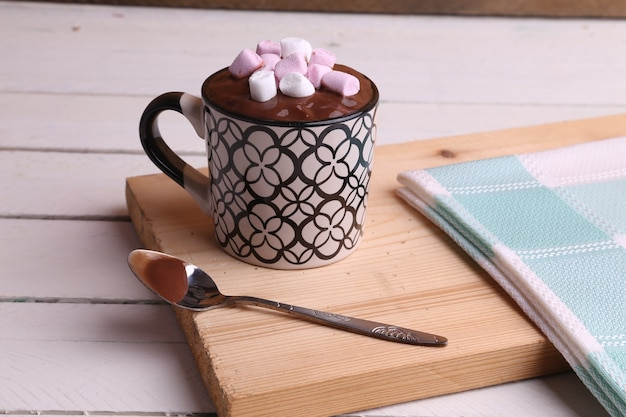 High angle shot of a cup of hot chocolate with marshmallows on a wooden surface