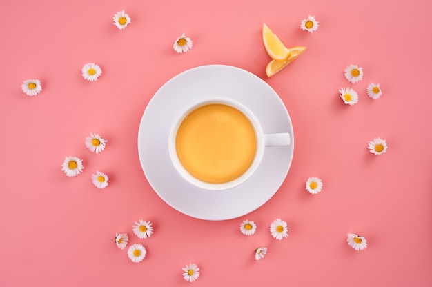 High angle shot of a cup of orange juice surrounded by small daisy flowers on a pink surface
