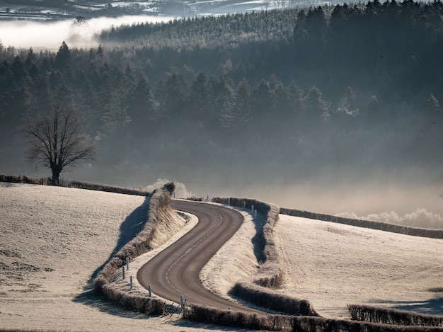 High angle shot of a curvy road in the middle of snowy fields with forested hills