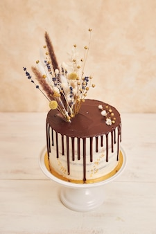 High angle shot of delicious boho cake with chocolate drip and flowers with golden decorations