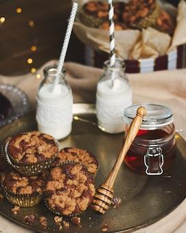 Colpo ad alto angolo di deliziosi muffin di biscotti di natale su un piatto con miele e latte