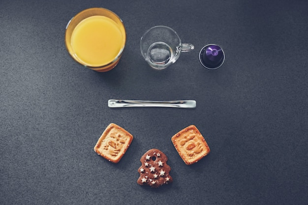 High angle shot of delicious cookies and glass cups with juice and water on a grey surface