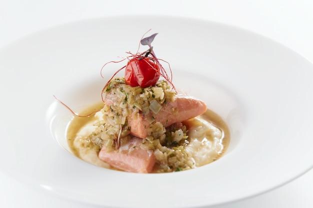 Colpo di alto angolo di un delizioso piatto con pesce e verdure in un piatto bianco