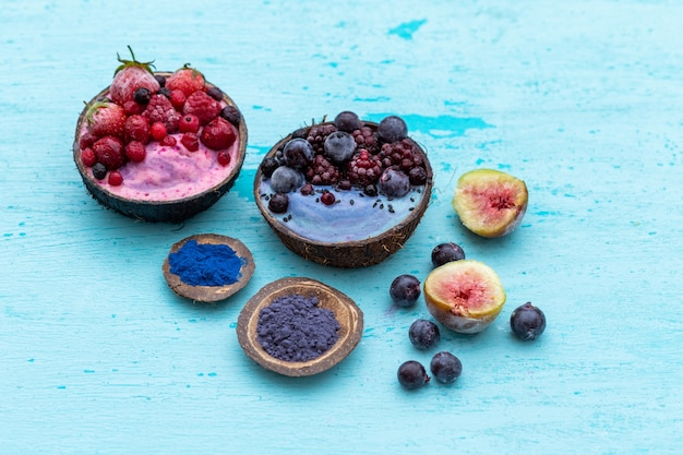 High angle shot of delicious fruit shakes topped with frozen fruits in coconut bowls