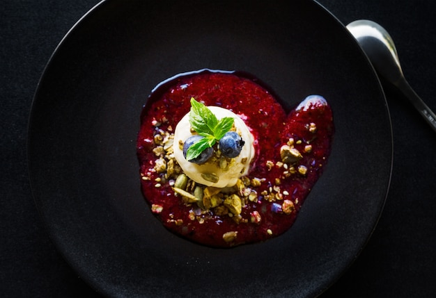 High angle shot of a delicious red dessert with white cream, berries and nuts in a black bowl