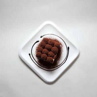 Colpo ad alto angolo di delizioso tiramisù in un piatto bianco su sfondo bianco