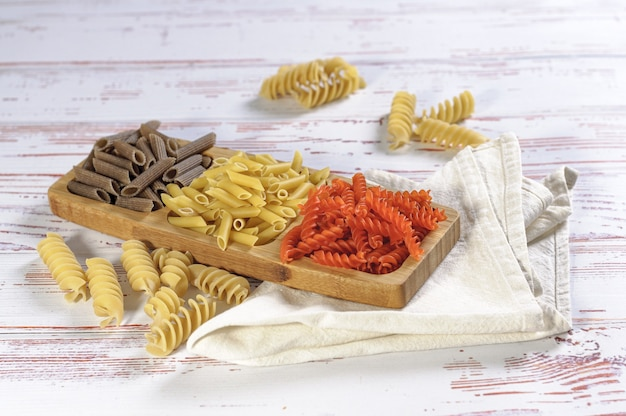 Colpo di alto angolo di diversi colori di pasta in un piatto di legno