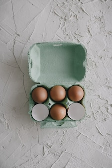High angle shot of eggs and eggshells in a box on the table