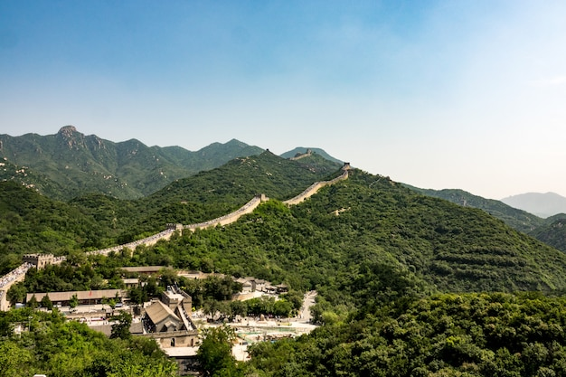 High angle shot of the famous great wall of china surrounded by green trees in summer