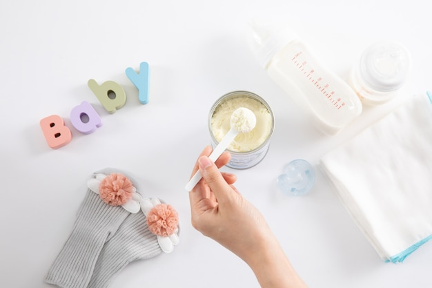 High angle shot of a female hand and baby care items on white surface
