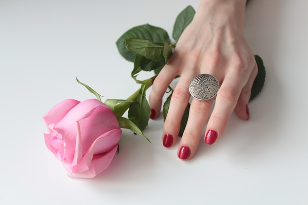 High angle shot of a female hand with a beautiful silver ring on a rose with green leaves