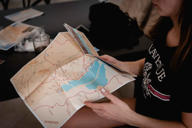 High angle shot of a female holding and reading a map in order to find her way