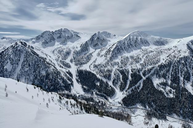 Alta angolazione di una montagna boscosa ricoperta di neve a col de la lombarde - isola