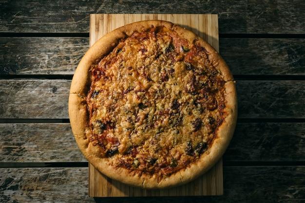 Colpo di alto angolo di una pizza appena sfornata su una superficie di legno
