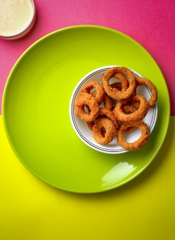 High angle shot of fried onion rings placed on a green plate