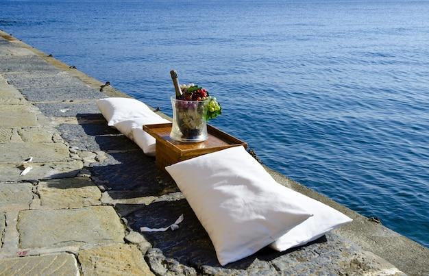 Colpo di alto angolo di un cesto di frutta e una bottiglia di champagne sul molo in riva al mare calmo