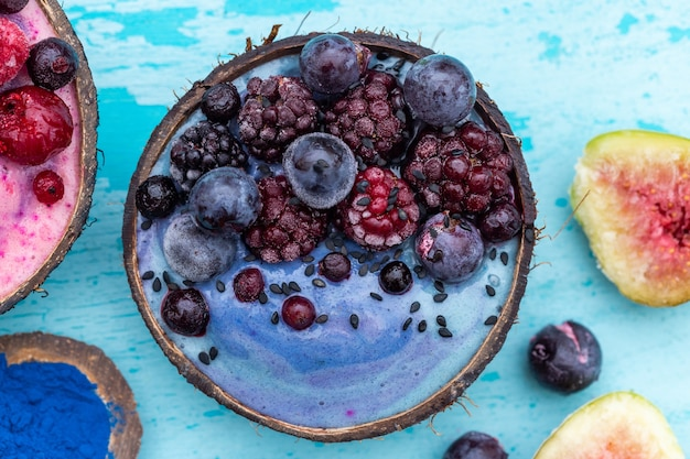 High angle  shot of a fruit shake topped with frozen raspberries and blueberries in a coconut bowl