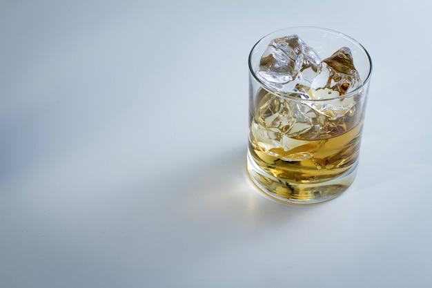 Colpo di alto angolo di un bicchiere pieno di ghiaccio e un po 'di whisky isolato su uno sfondo bianco